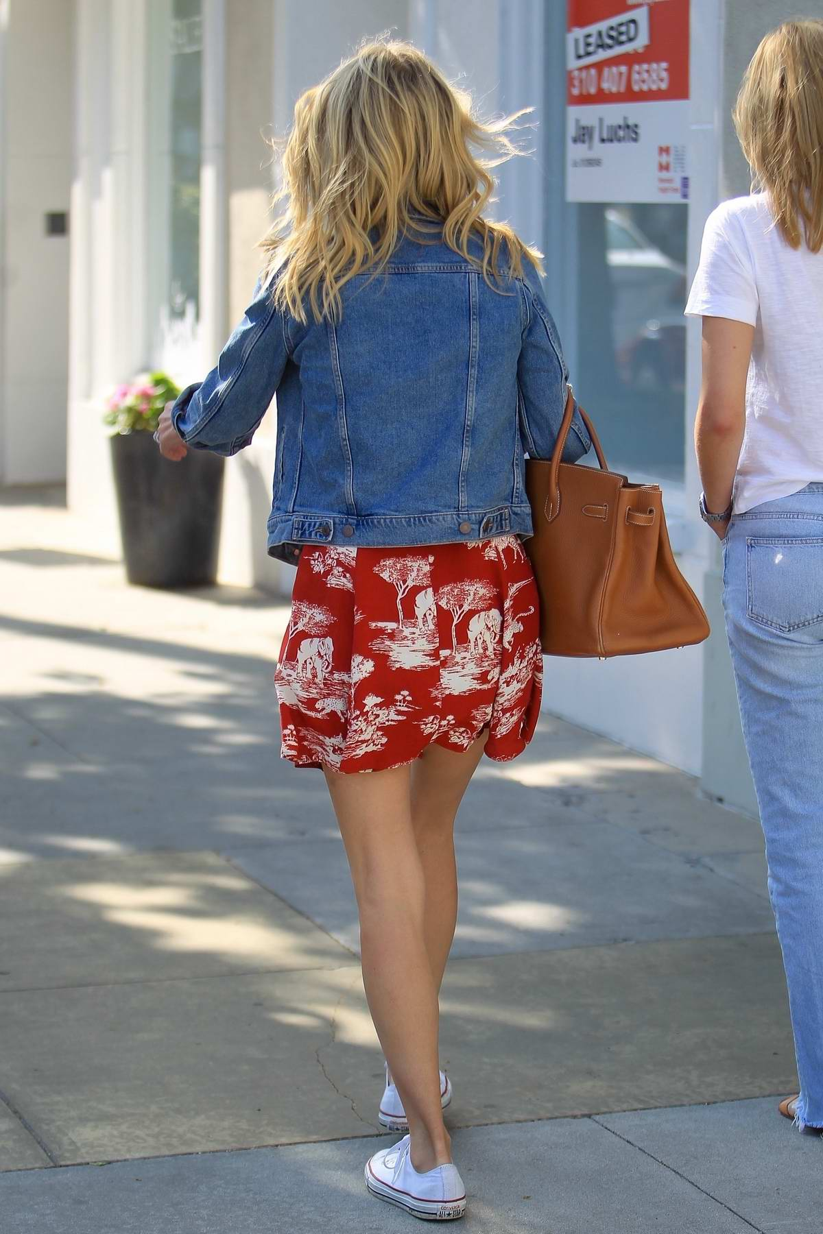 f768eb98bcb1 nicky hilton wears a short red dress and denim jacket with a pair of ...