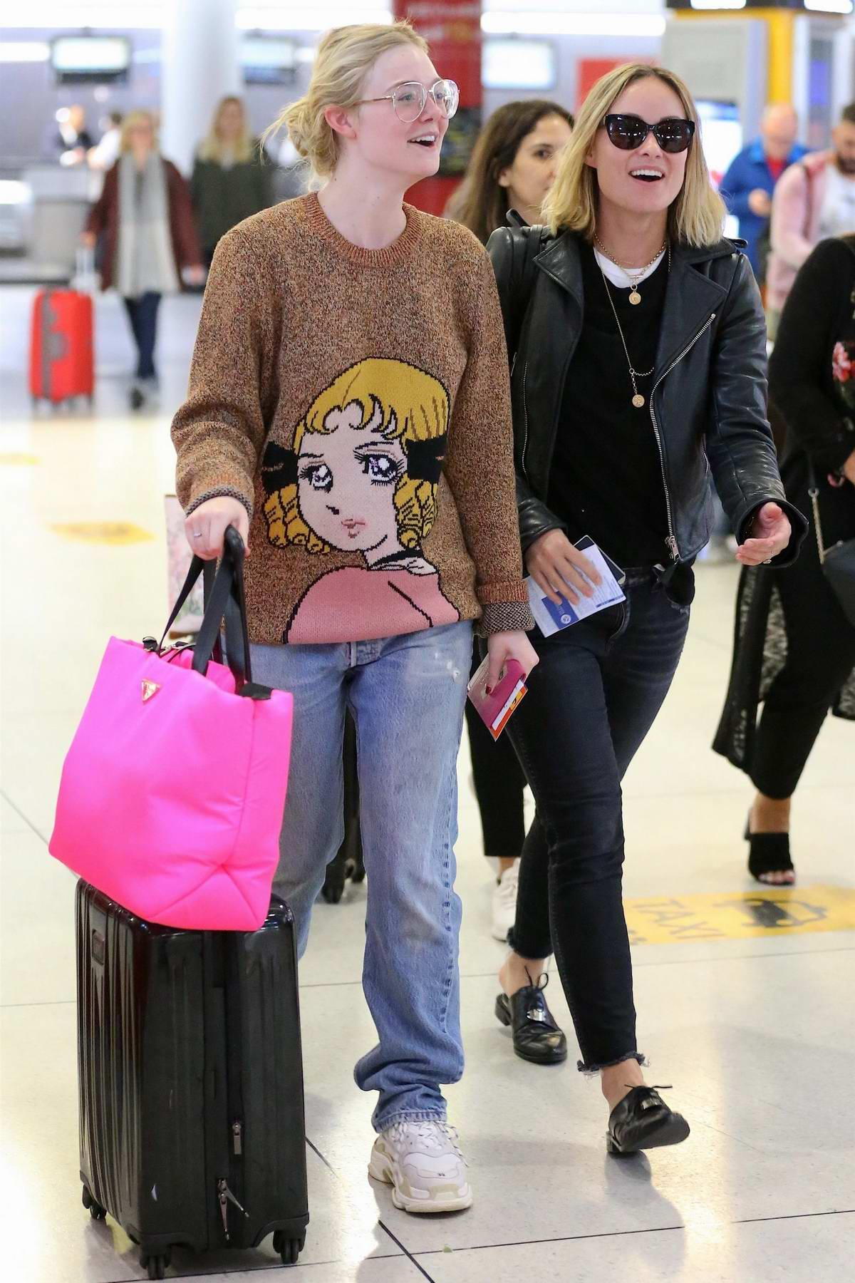 Olivia Wilde and Elle Fanning share a laugh as they arrive together at JFK airport in New York City