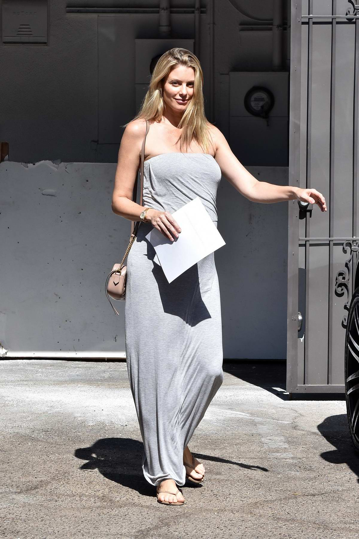 Paige Butcher wears a gray strapless maxi dress while running errands in Los Angeles