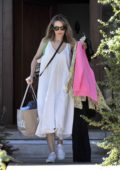 Rachel McAdams spotted carrying shopping bags and clothes as she heads out wearing a white sundress and sneakers in Los Angeles