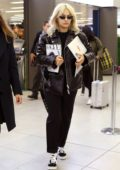 Rita Ora is seen holding her laptop and an edition of Vogue Italia magazine as she arrives at the airport in Milan, Italy
