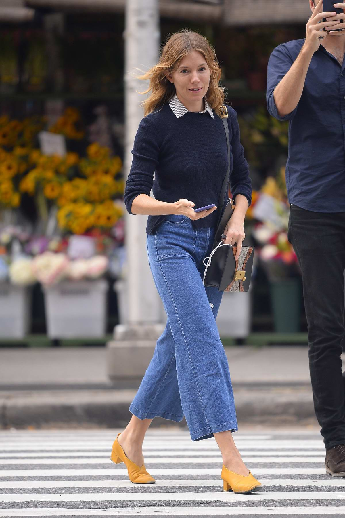 Sienna Miller wears blue sweater, flared jeans paired with mustard colored shoes while out in New York City