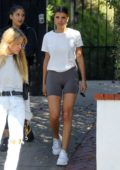 Sofia Richie wears a white top and biker shorts while out shopping with a friend in Los Angeles