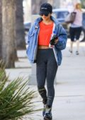 Vanessa Hudgens keeps it casual in an orange top with a denim jacket and leggings while out shopping at Sephora in Los Angeles