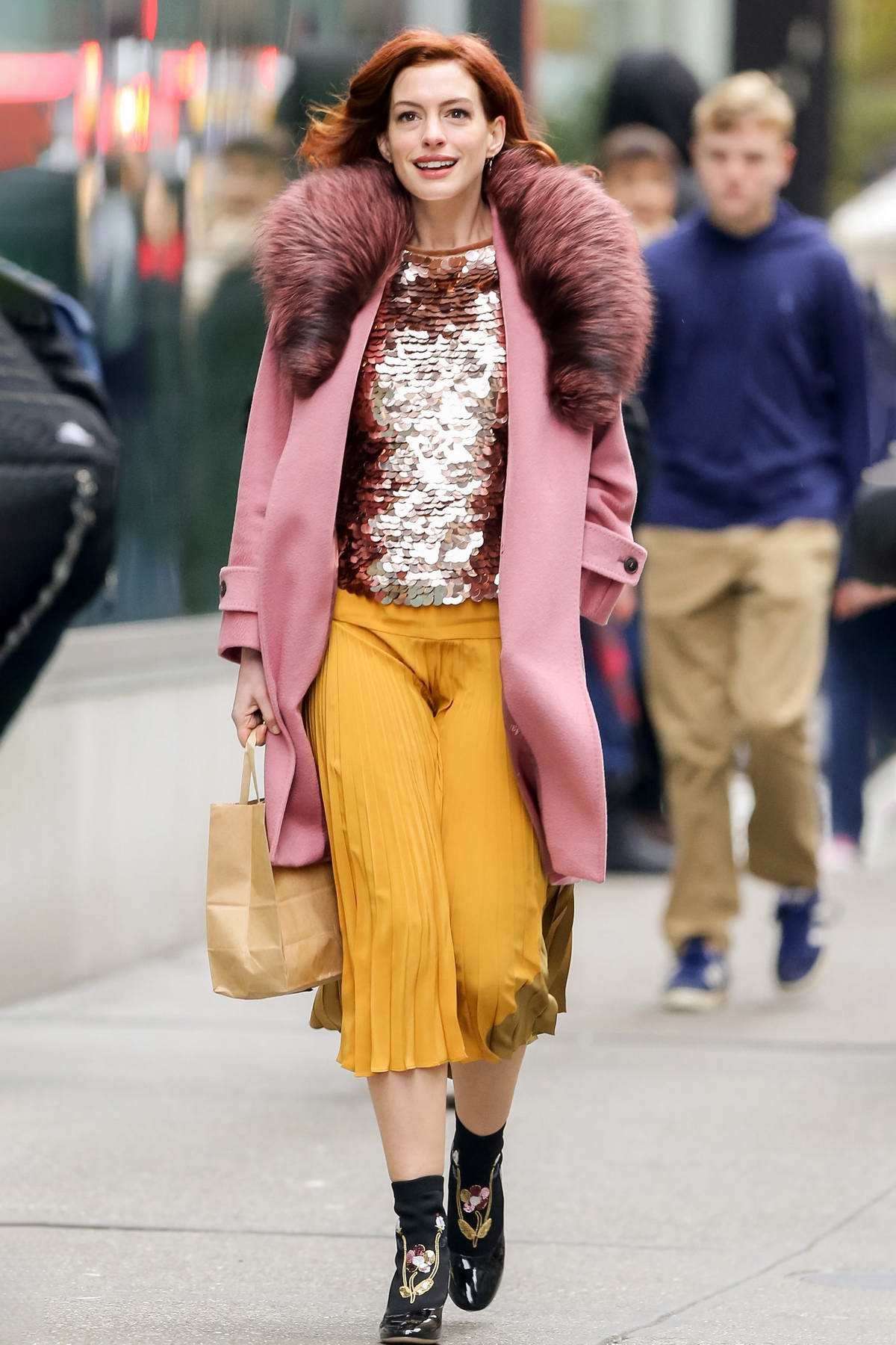 Anne Hathaway looks striking in a fur-trimmed pink coat paired with sequined top and yellow shirt as she steps out in New York City
