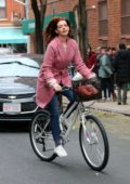 Anne Hathaway seen riding a bike in a pink trench coat while filming upcoming TV series 'Modern Love' in New York City