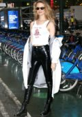 Behati Prinsloo poses in a white tank top and black leather pants as she leaves Victoria's Secret offices in New York City