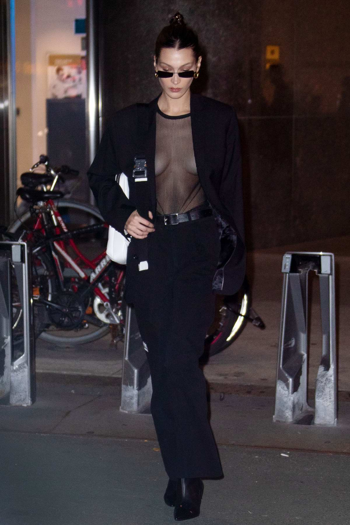 Bella Hadid wears a black blazer over a sheer top as she leaves Victoria's Secret offices in New York City