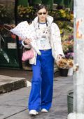 Bella Hadid wore a white puffer jacket, Dior top and blue flared pants while shopping for some party supplies and flowers in New York City