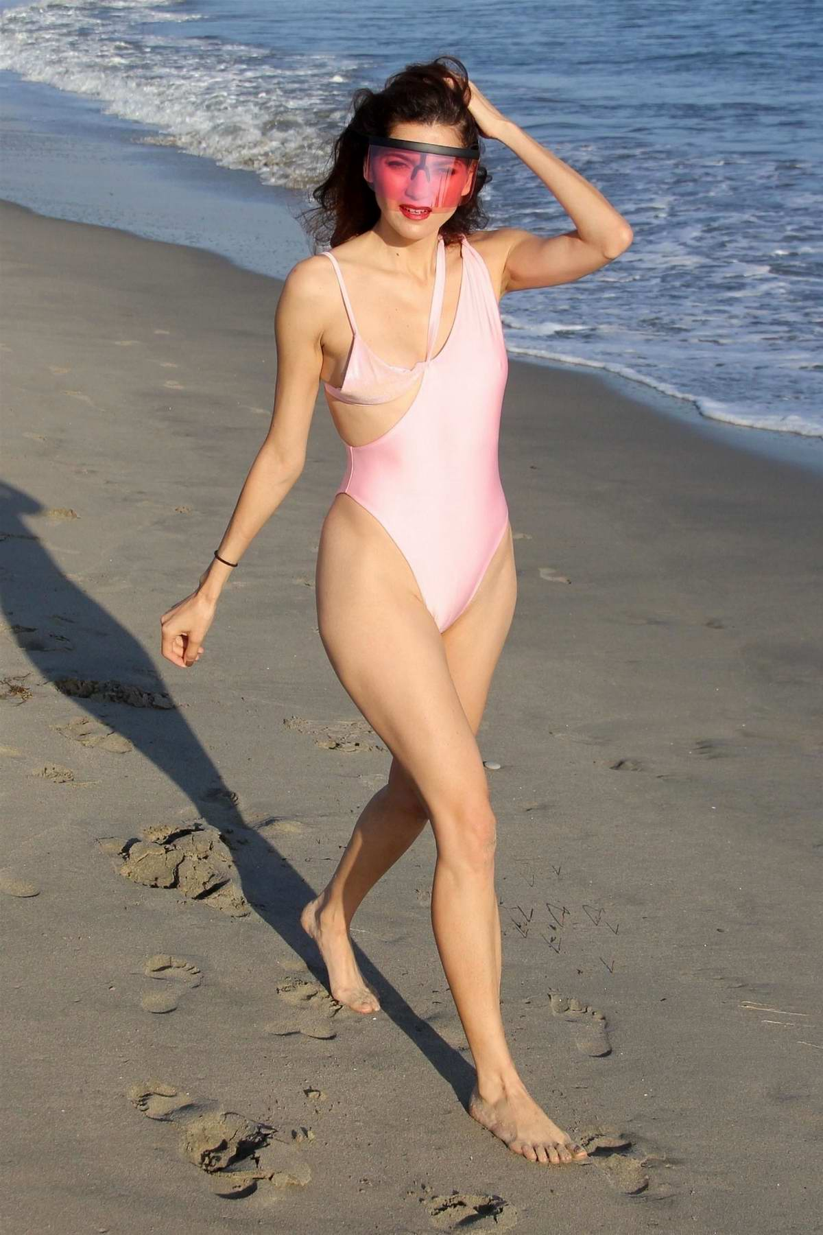 Blanca Blanco wears soft pink swimsuit with a pair of large pink sunglasses as she enjoys another day on the beach in Malibu, California