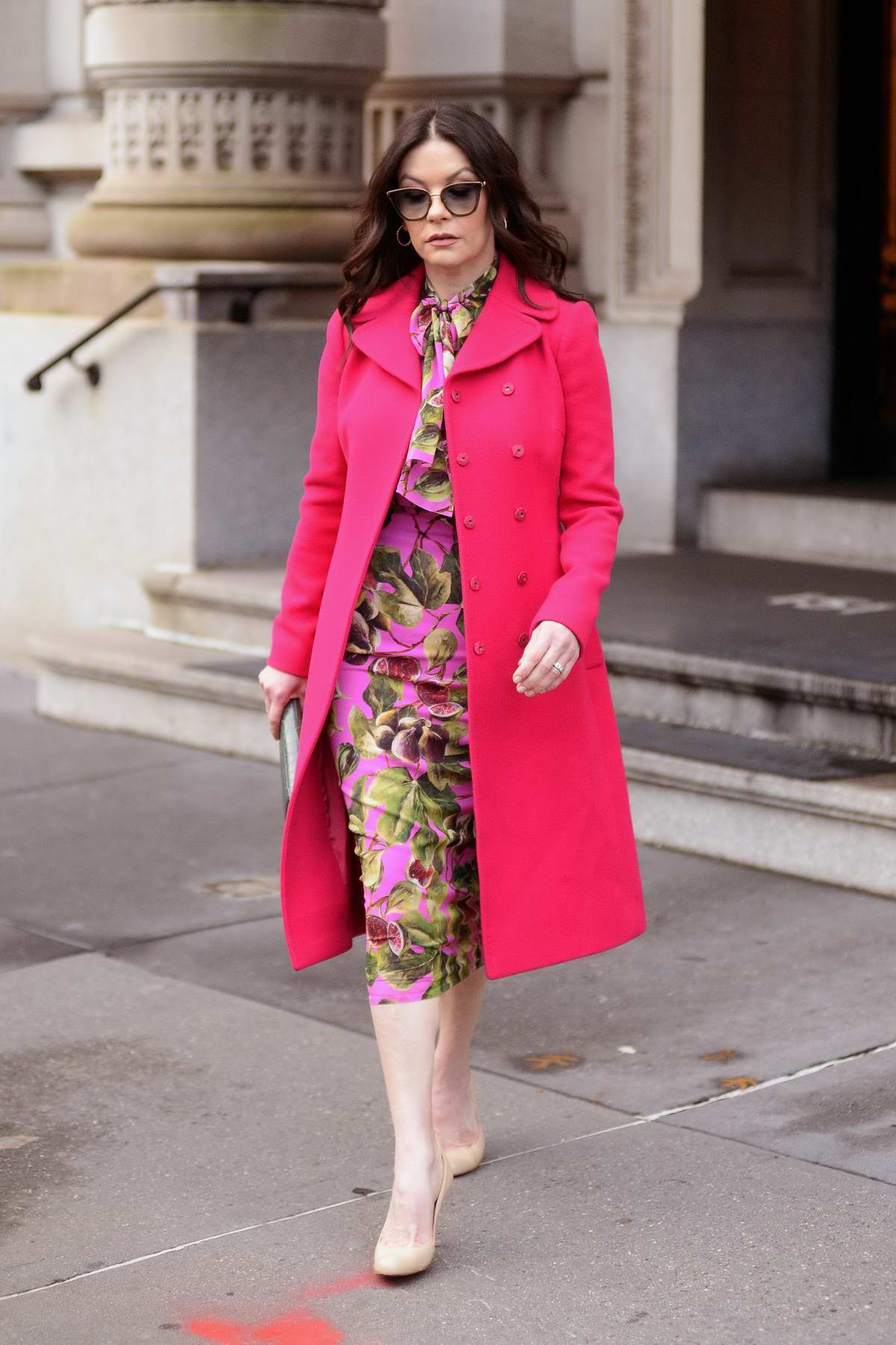 Catherine Zeta-Jones wore fuchsia pink coat with a floral print dress as she leaves her apartment in New York City