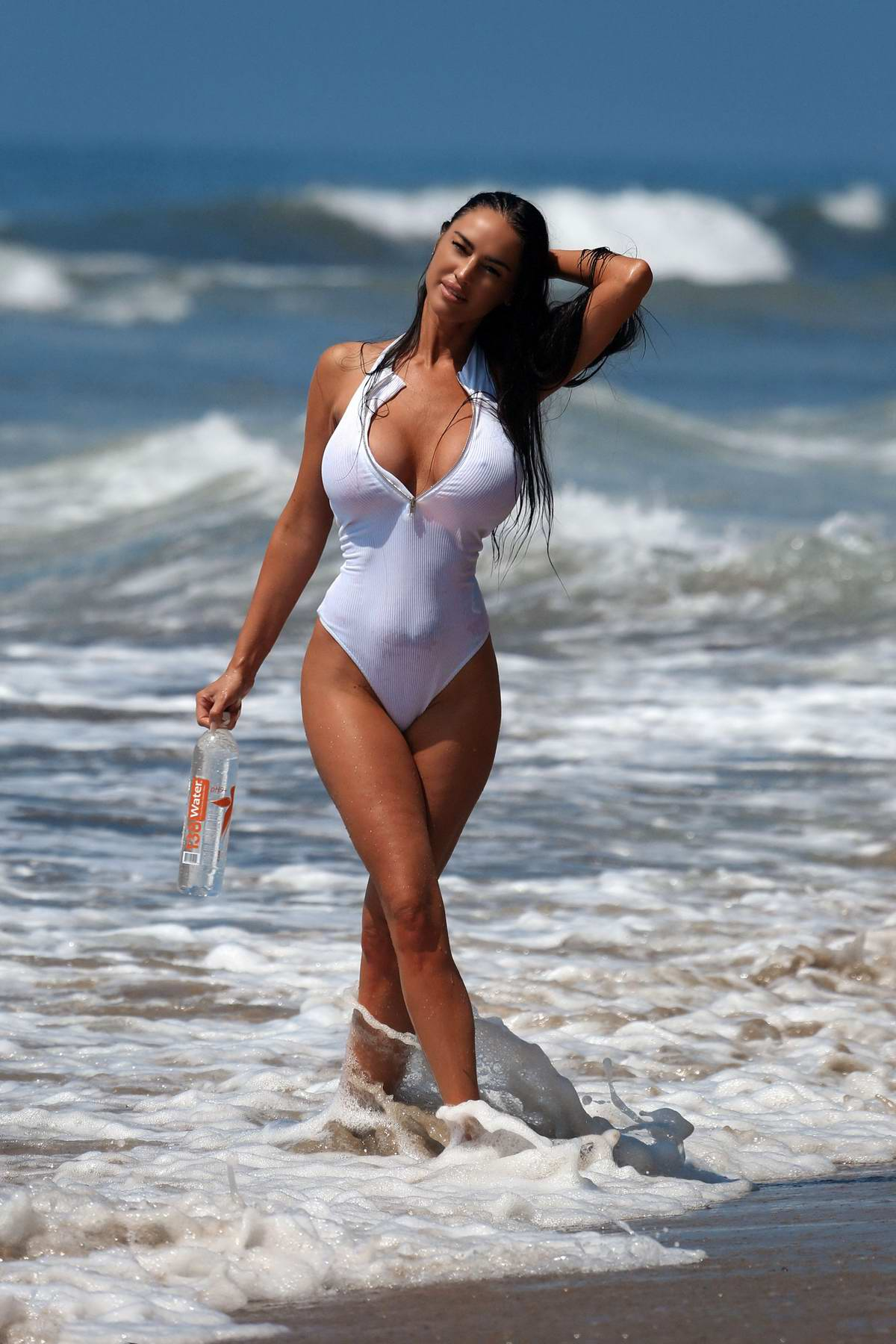 Charlie Riina seen wearing a white swimsuit during a beach photoshoot for 138 Water in Santa Monica, California