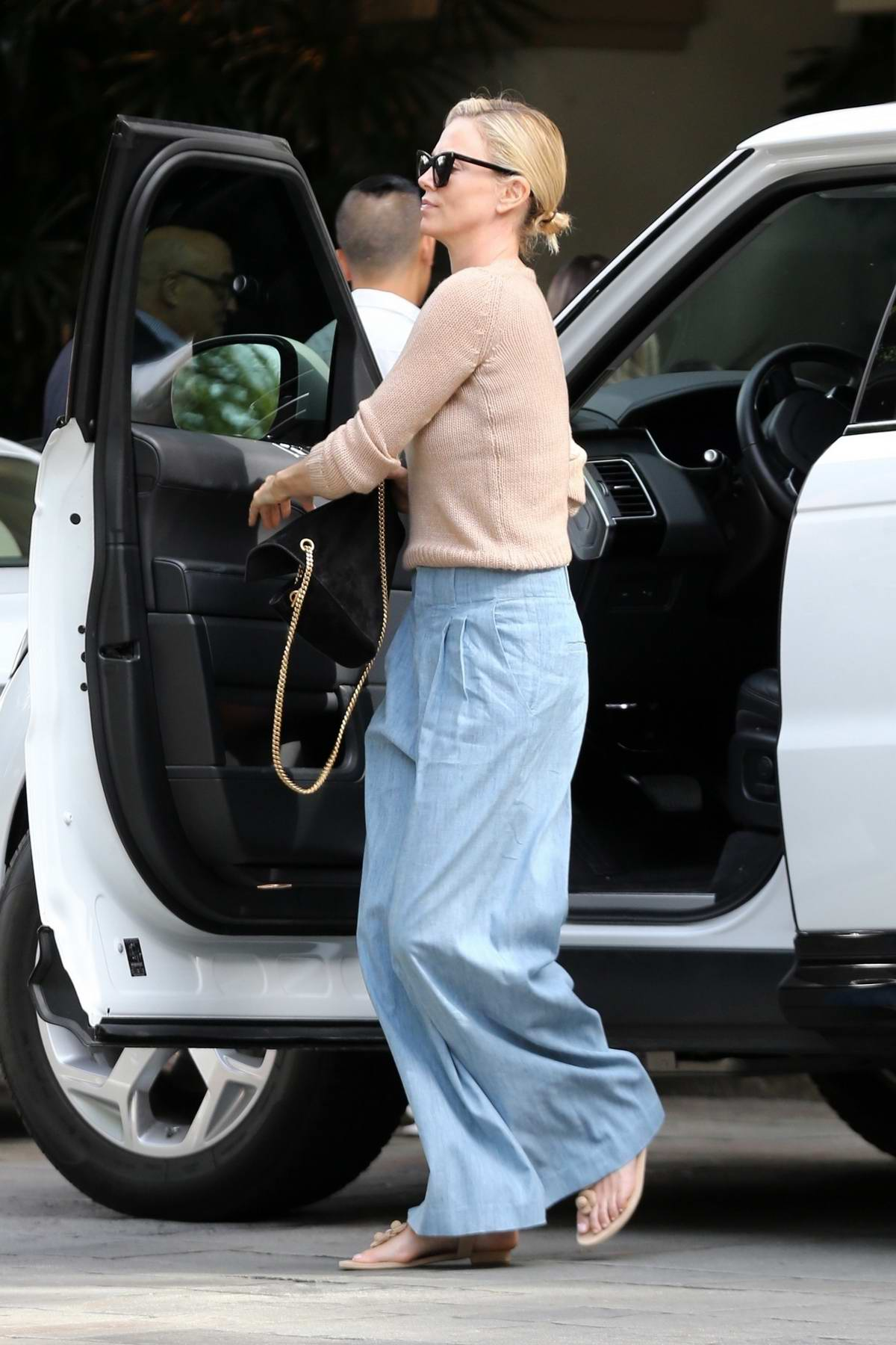Charlize Theron wears a pair of flared jeans and sweater as she takes her kids to lunch in Beverly Hills, Los Angeles