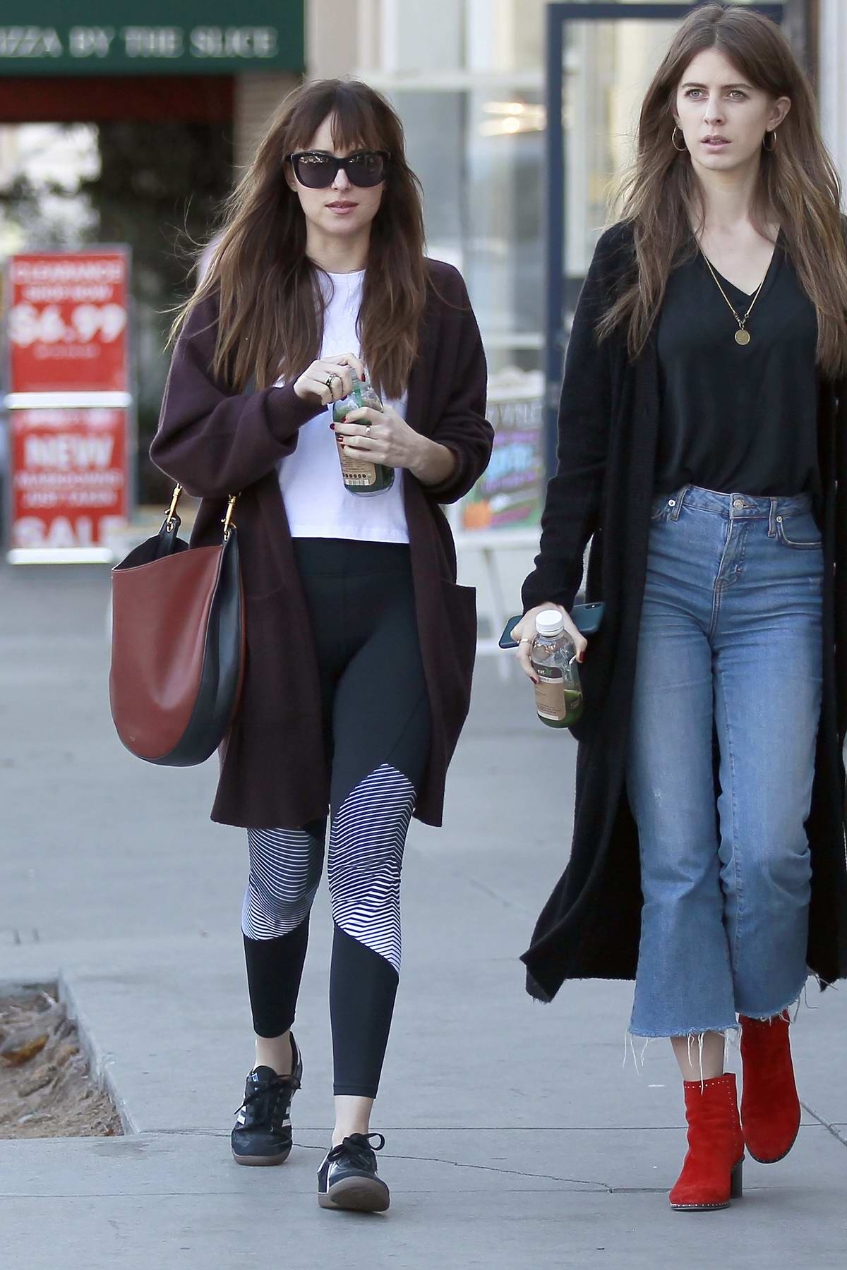 Dakota Johnson seen having chat with a friend while picking up some green juice at Kreation in Los Angeles