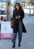Dakota Johnson steps out in a black coat and jeans as she heads for a lunch meeting in Los Angeles