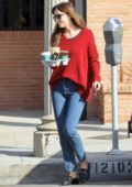Dakota Johnson wears a red sweater and jeans as she grabs coffee at Alfred Coffee in Los Angeles
