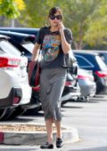 Dakota Johnson wore a graphic t-shirt, grey skirt with a pair of Gucci shoes while picked up some groceries from Erewhon in Los Angeles