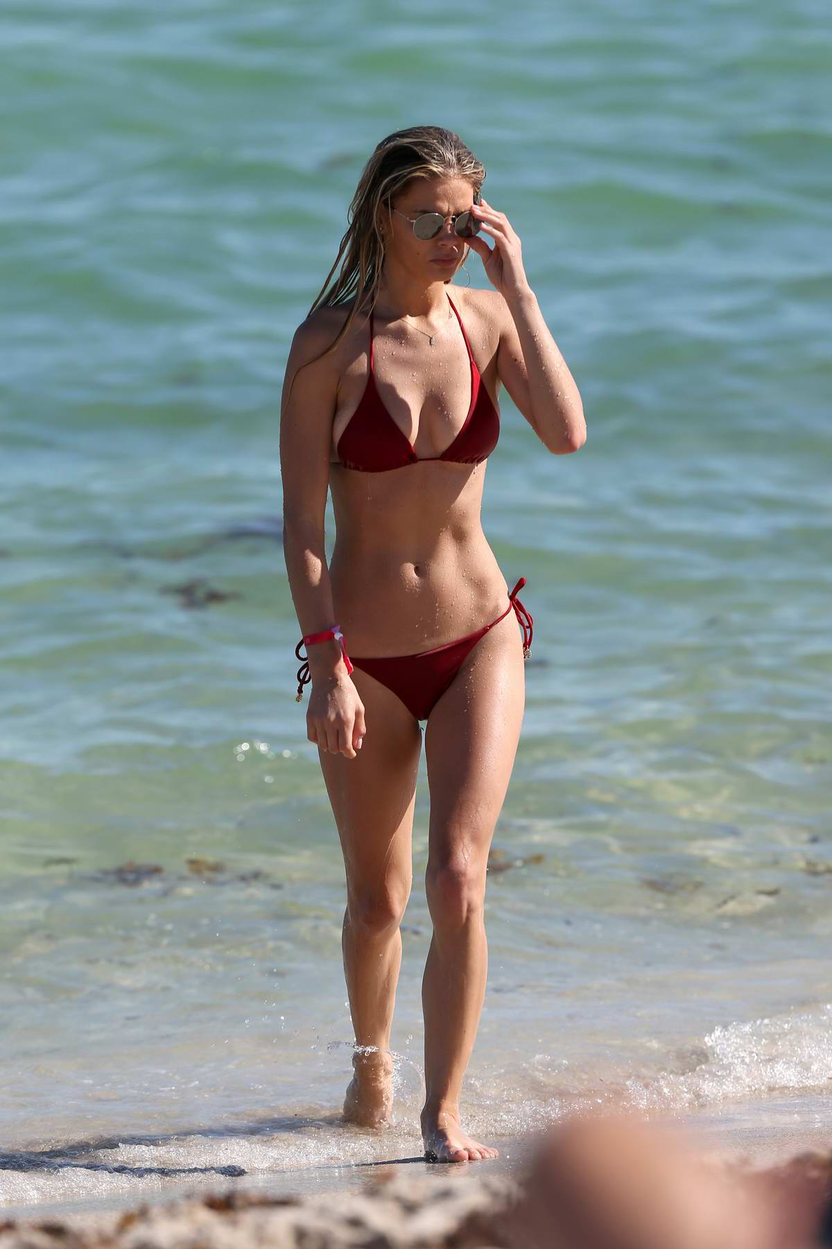 Danielle Knudson hits the ocean in a red bikini on Miami Beach, Florida