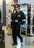 Dua Lipa rocks a lace-trimmed puffer jacket, track pants and Louis Vuitton sneakers as she arrives at the Tegel airport in Berlin, Germany