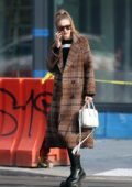 Gigi Hadid busy on her phone while out in a tweed coat in New York City