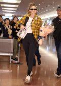 Gigi Hadid rocks yellow plaid jacket and black leggings as she touches down at Haneda International Airport in Tokyo, Japan