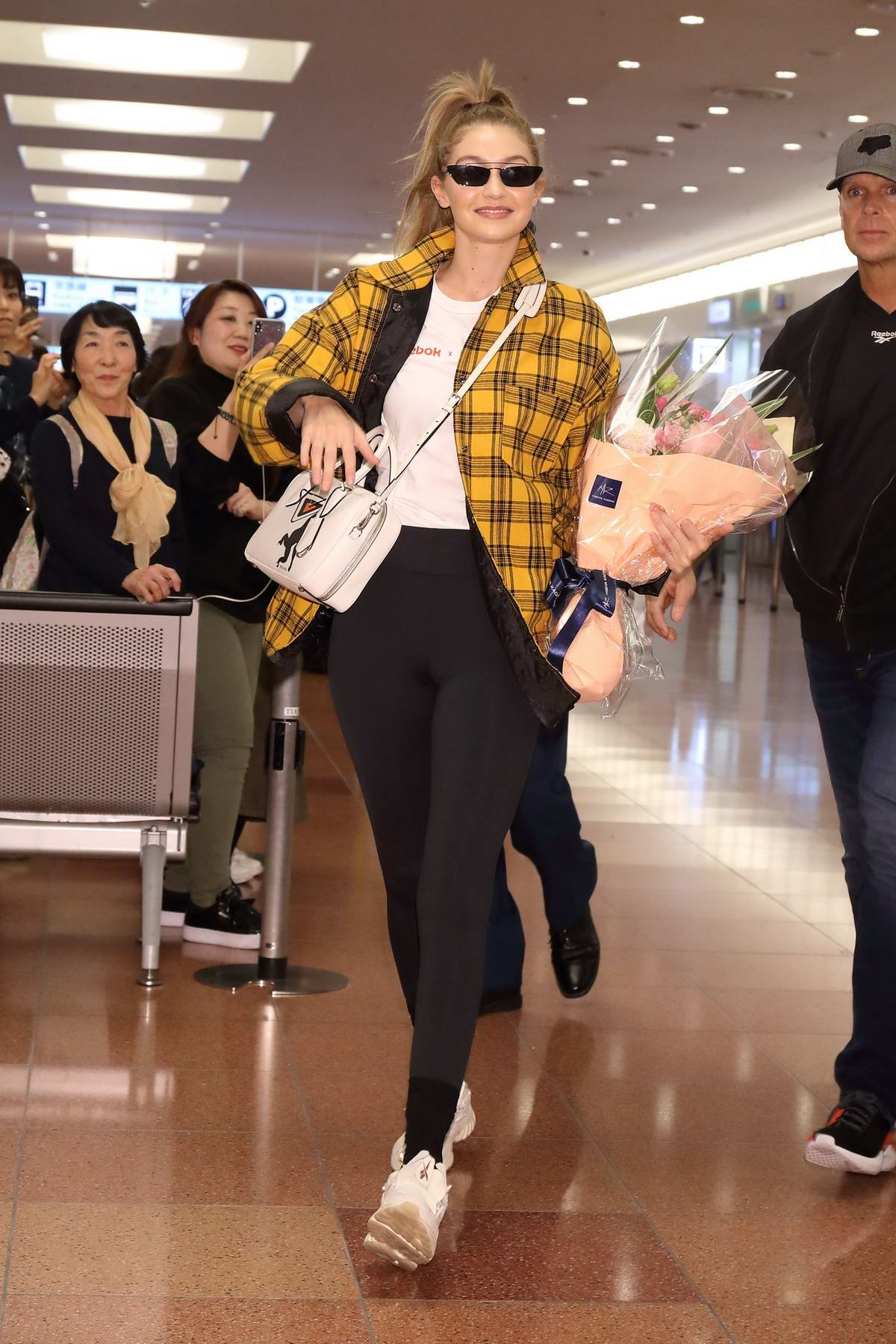 Gigi Hadid rocks yellow plaid jacket and black leggings as she touches down at Haneda International Airport in Tokyo, Japan