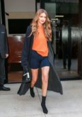 Gigi Hadid steps out in an orange hoodie and black biker shorts while leaving her apartment in New York City
