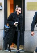 Hailey Baldwin keeps it warm in a black fur coat over a black hoodie and leggings while visiting a doctor's office in Manhattan, New York City