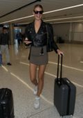 Hailey Clauson rocked a black leather jacket paired with brown miniskirt and white sneakers as she arrives at LAX airport in Los Angeles