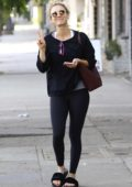 Kaley Cuoco flashes the peach sign with a smile as she run errands after leaving her pilates class in Los Angeles
