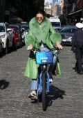 Kendall Jenner seen wearing a fur-trimmed green trench coat while out riding a Citi Bike with friends in SoHo, New York City