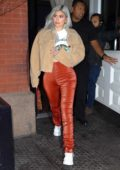 Kylie Jenner rocks a beige sherpa jacket with orange pants as she heads to Travis Scott's concert at Madison Square Garden in New York City