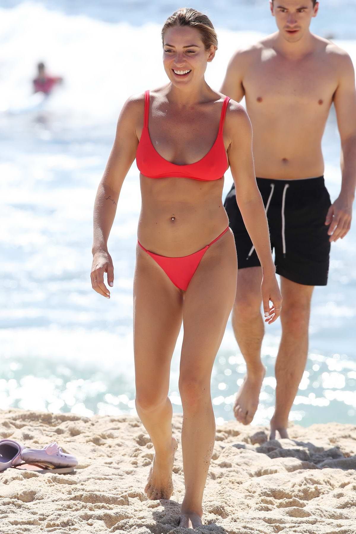 Lisa Clark seen wearing a red bikini during a beach outing with a male friend in Sydney, Australia