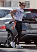Margot Robbie wears white 'Champ' tee and black leggings as she leaves the gym holding an umbrella in Los Angleles