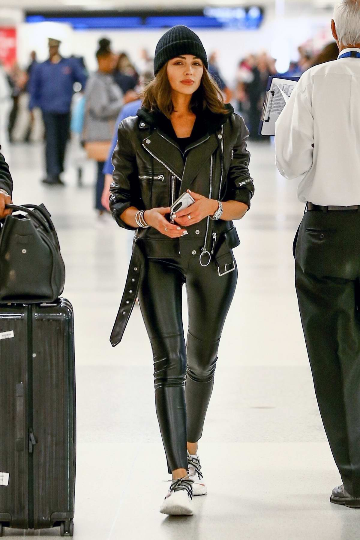 Olivia Culpo looks chic in a black leather jacket paired with matching leather tights and white sneakers as she arrives at the Miami International Airport, Florida