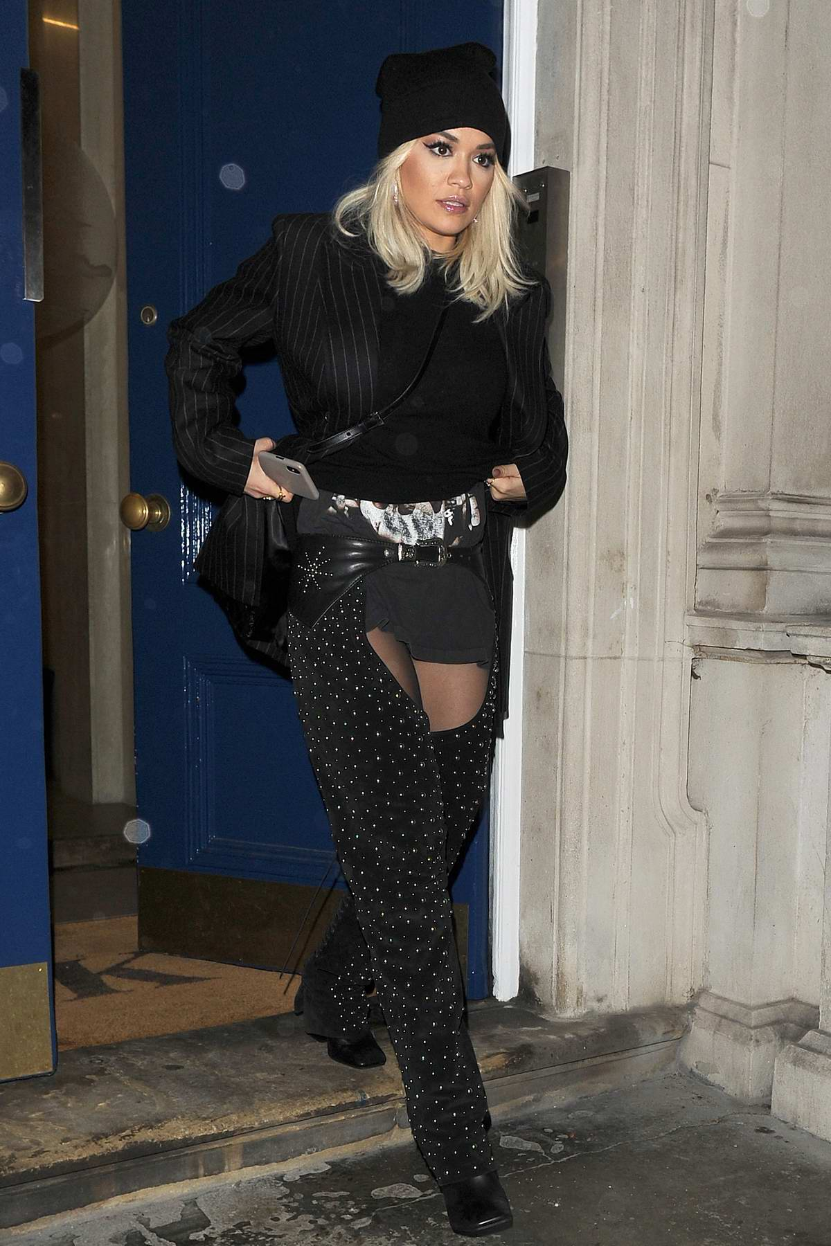 Rita Ora rocks a pair of black chaps with pinstripe blazer, black jumper and a beanie while she heads for a night out in London, UK