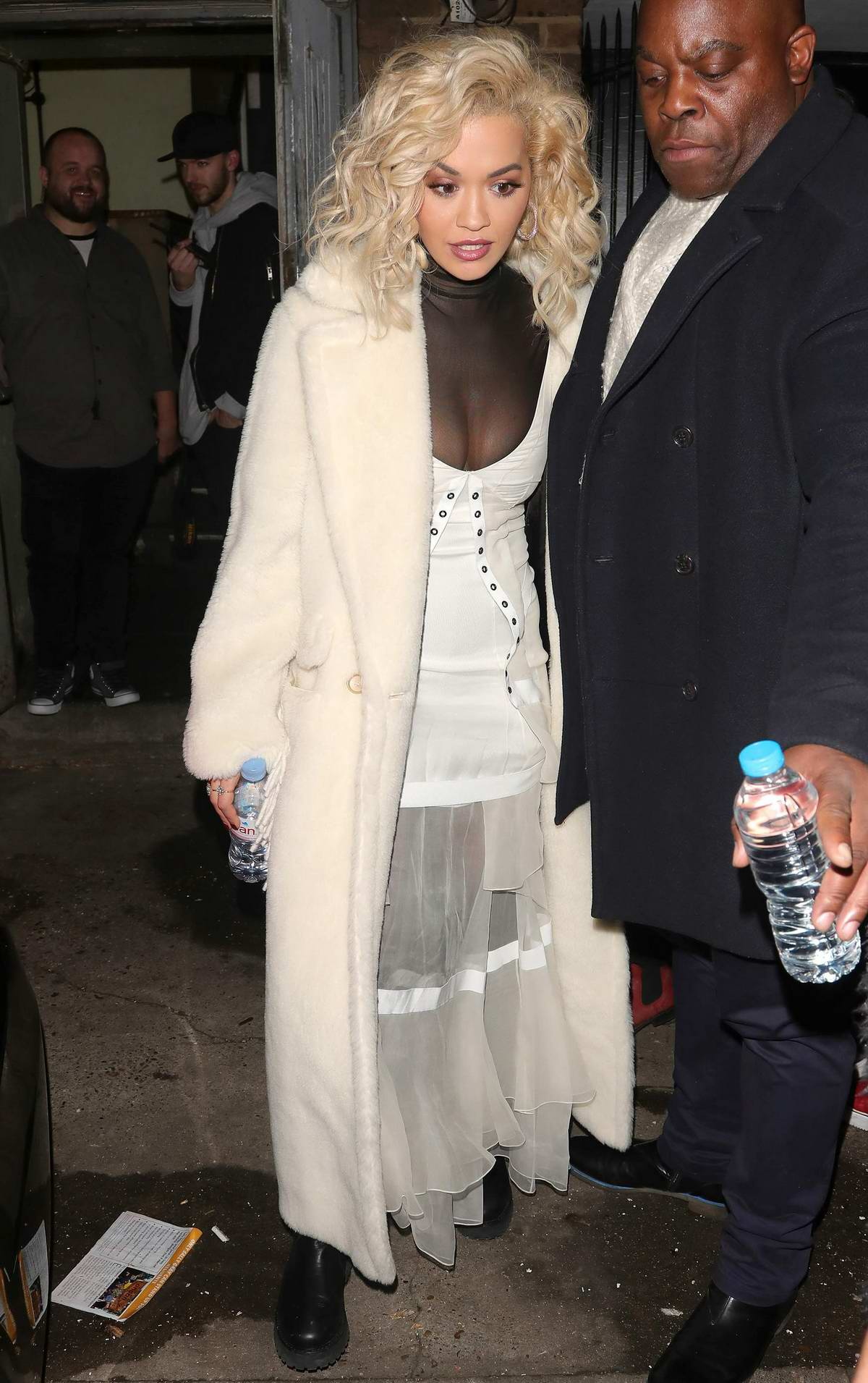 Rita Ora seen wearing a black and white sheer dress with a long coat as she leaves Notting Hill Art's Club in London, UK