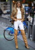 Romee Strijd wears a pair of thigh high cowboy boots with matching denim jacket, white jeans and top while visiting Victoria's Secret offices in New York City