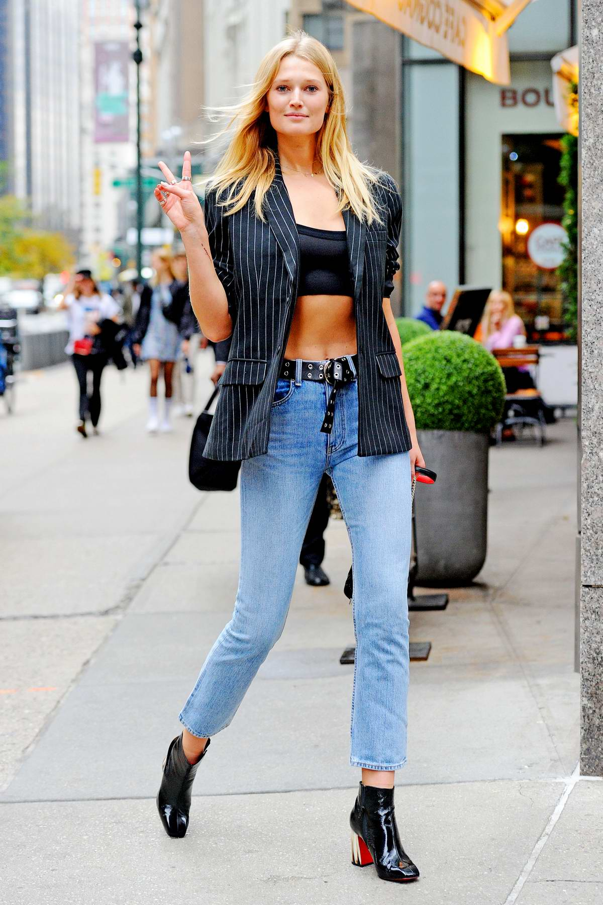 Toni Garrn stuns in a pinstriped blazer paired with a crop top, jeans and black boots as she leaves the Victoria's Secret offices in New York City