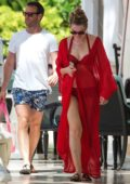 Zoe Salmon wears a bright red cover-up gown over her bikini while enjoying her vacation with husband William Corrie in Bridgetown, Barbados