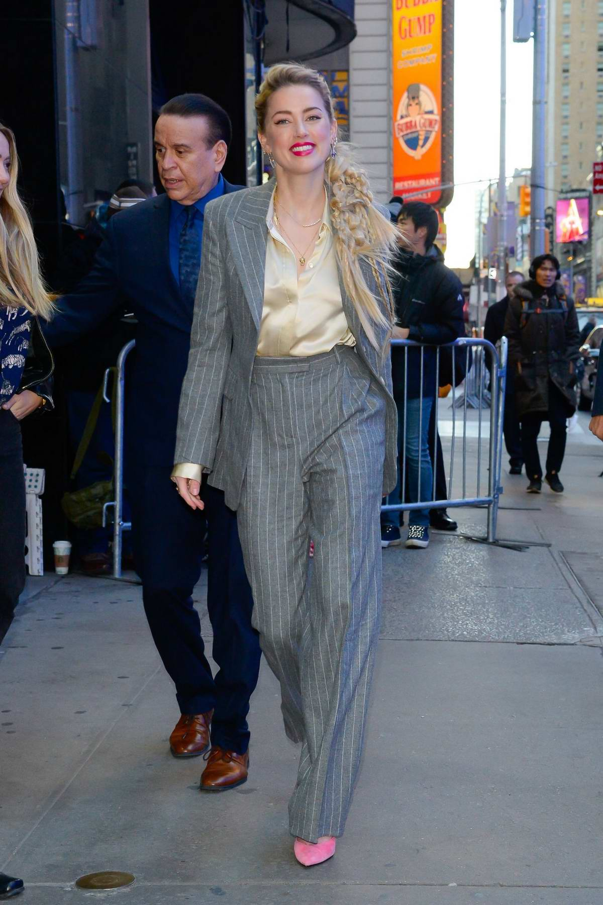 Amber Heard wears a pinstriped grey suit as she arrives at 'Good Morning America' studios in New York City