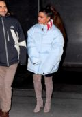 Ariana Grande bundles up in a baby blue puffer jacket and knee high boots as she heads out in New York City