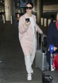 Camila Morrone stopped to exchange some money after she touched down at LAX airport in Los Angeles