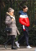 Emily Ratajkowski seen in a blue, white and red Levi's puffer jacket and Puma sweatpants while out on stroll with her parents in New York City