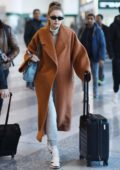 Gigi Hadid wore a brown long coat with grey turtleneck and sweatpants as she arrives at the airport to fly out of Milan, Italy