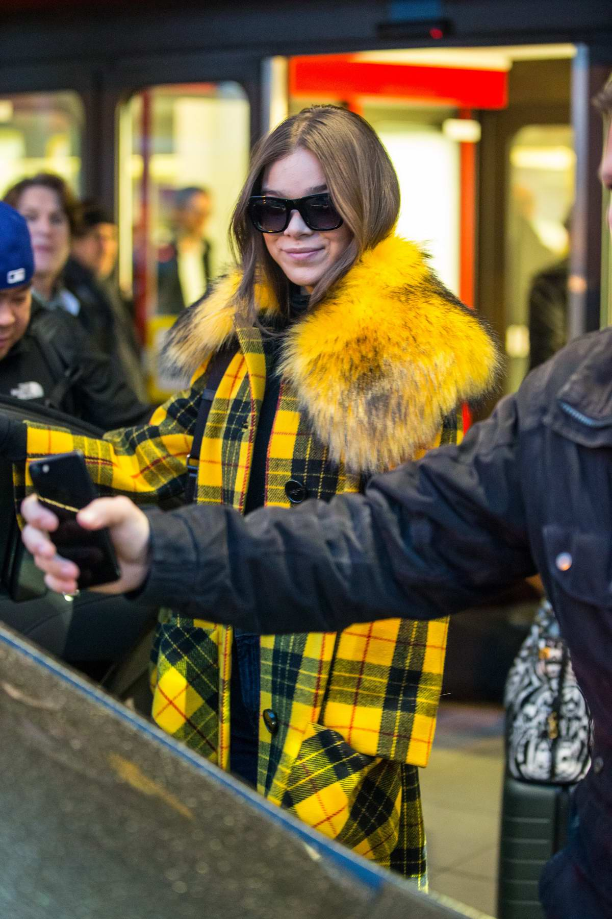 Hailee Steinfeld wears a fur-lined yellow and black plaid coat as she arrives at Berlin Tegel airport to promote Bumblebee in Germany