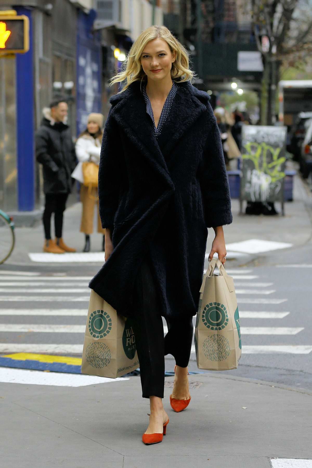Karlie Kloss walks home carrying two bags of groceries from Whole Foods in New York City