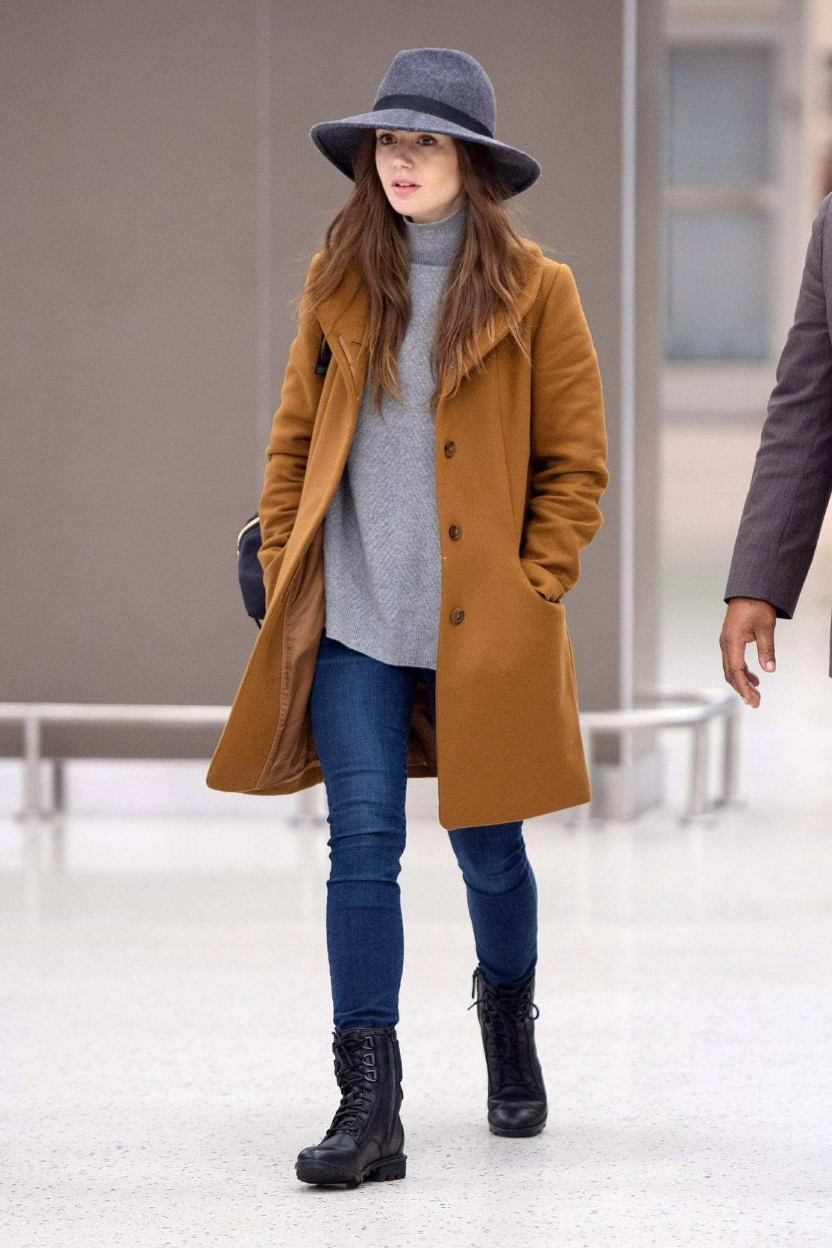 Lily Ccollins seen wearing a hat with brown coat, turtleneck and jeans as she arrives at JFK airport in New York City