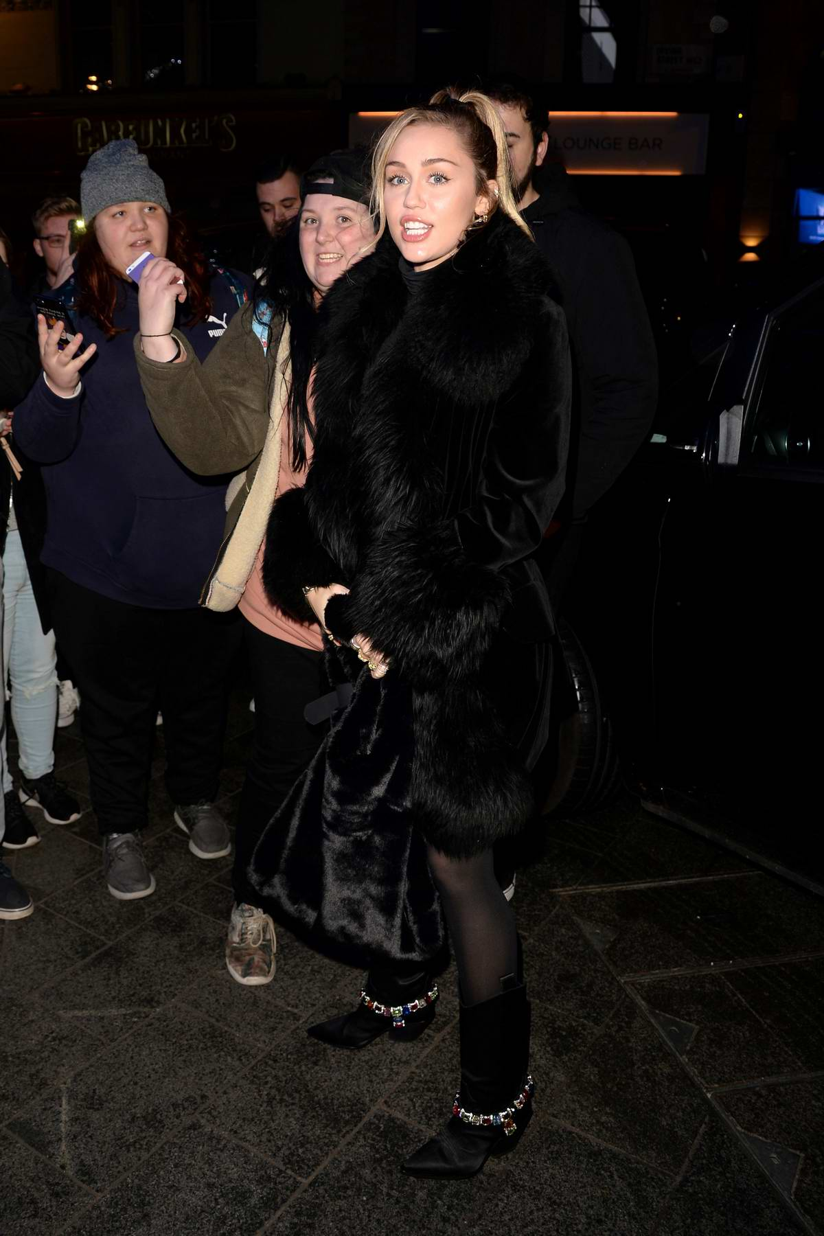 Miley Cyrus greets her fans while visiting the Capital Radio in London, UK