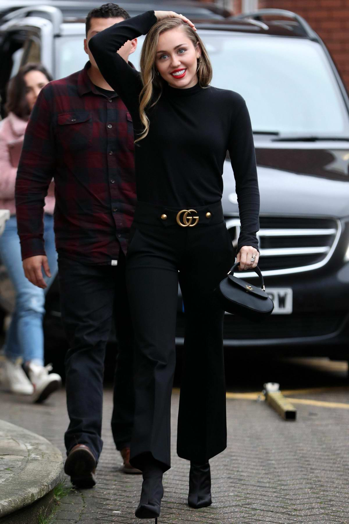 Miley Cyrus is all smiles as she greets her fans while out in an all black ensemble in London, UK